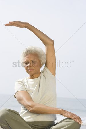 Arm raised : Senior woman sits in yoga pose