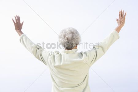 Jacket : Senior woman stands facing sea with arms raised