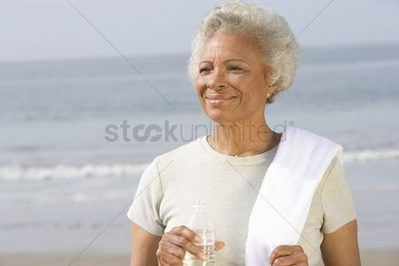 Fitness : Senior woman stands with drinking water and towel over her shoulder on beach