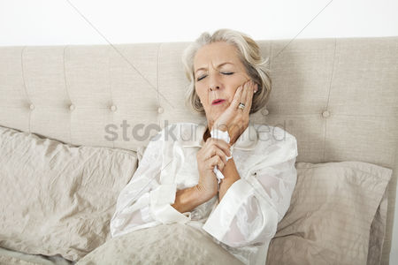 Pain : Senior woman suffering from toothache resting in bed