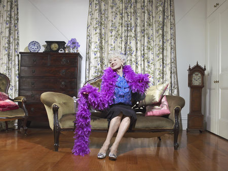 Fashion : Senior woman wearing feather boa sitting on love seat in living room  portrait