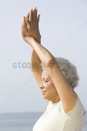 Arm raised : Senior woman with eyes closed in yoga pose