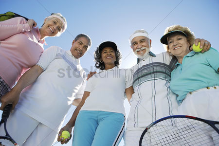 Seniors : Seniors standing in half circle holding rackets and balls low angle view