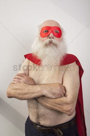 Bald : Shirtless senior man in super hero costume against white background