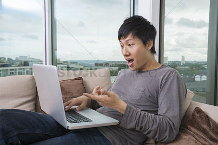 30s adult : Shocked man using laptop on sofa at home