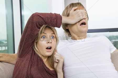 Couples : Shocked woman covering man s eyes while watching tv at home