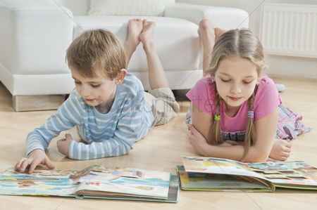 Czech republic : Siblings reading story books on floor in the living room