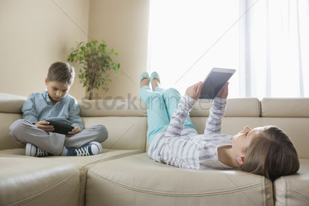 Pre teen : Siblings using technologies on sofa at home