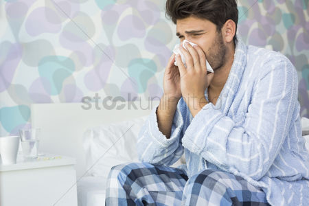 Blowing : Sick man blowing his nose in tissue paper on bed at home
