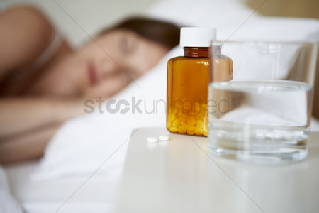 Medication : Sick woman in bed by pills on bedside table focus on foreground