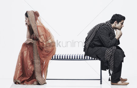 Ignorance : Side profile of a newlywed couple sitting on opposite ends of a bench