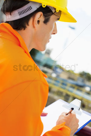 Supervisor : Side view of construction worker writing on clipboard at construction site