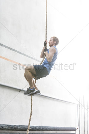 Rope : Side view of determined man climbing rope in crossfit gym