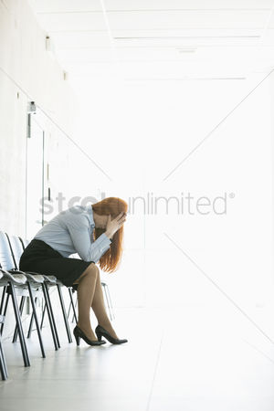 Worry : Side view of frustrated businesswoman sitting on chair in office