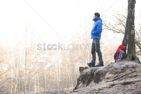 Remote : Side view of hiker standing on edge of cliff in forest
