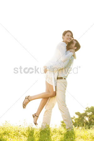 Girlfriend : Side view of man lifting woman in park against clear sky