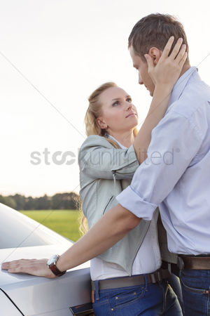 Land : Side view of romantic young couple by car at countryside