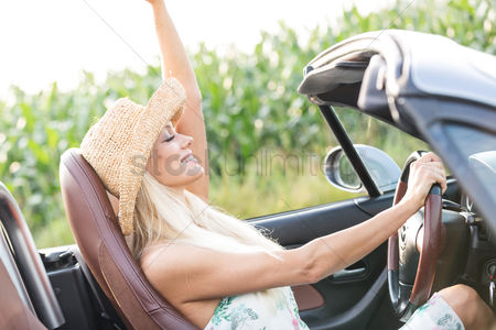 On the road : Side view of woman enjoying ride in convertible outdoors