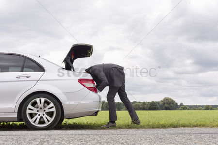 Land : Side view of young businessman looking in trunk of car at countryside