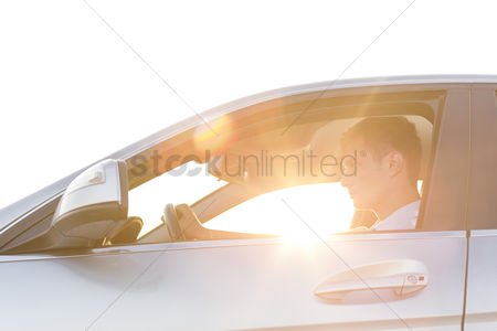 Land : Side view of young man driving car