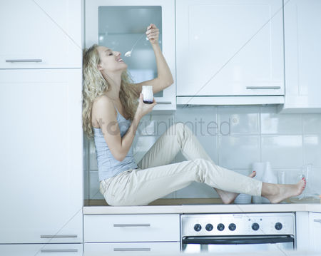 Czech republic : Side view of young woman eating yogurt while sitting on kitchen counter