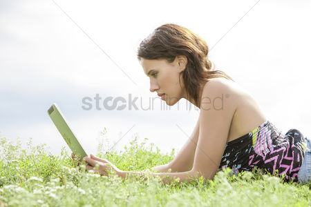 Grass background : Side view of young woman using tablet pc while lying on grass against sky