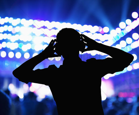 Dance : Silhouette of dj wearing headphones and performing at a night club
