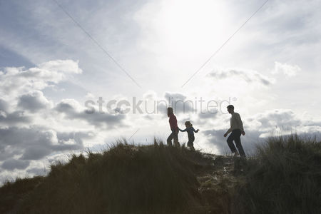 Grass : Silhouette of parents and daughter  5-6  walking on sand dunes