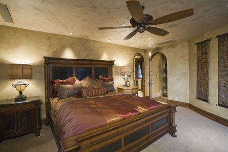 Us : Silk bedcover on antique bed in palm springs home