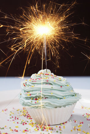 Black background : Single cupcake with lit sparkler