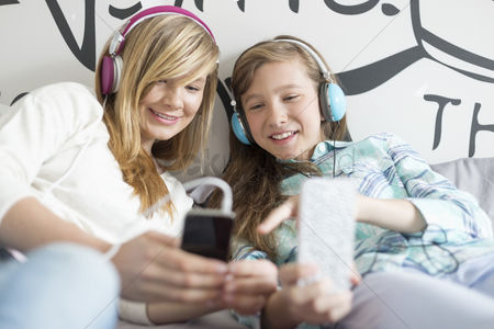 Cell phone : Sisters listening music through headphones at home