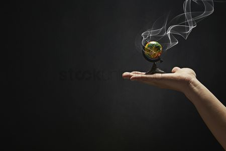 Black background : Small globe placed on human hand