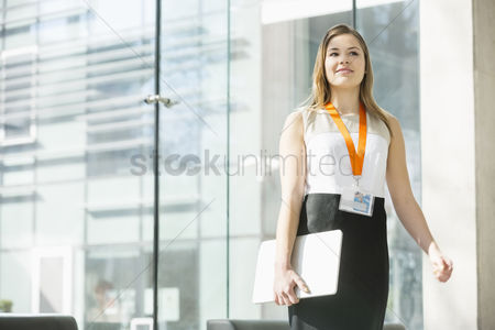 Occupation : Smiling businesswoman holding laptop while standing in office