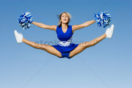 Physical : Smiling cheerleader jumping in mid-air  portrait