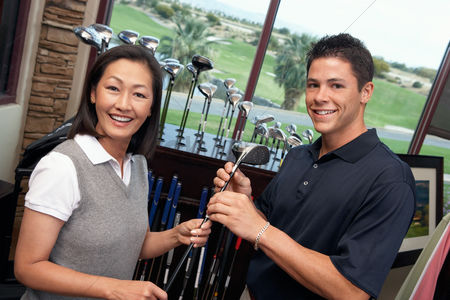 Club : Smiling clerk assisting mid-adult woman shopping for golf clubs in golf shop
