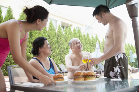 Toasting : Smiling family eating hamburgers by the pool on vacation
