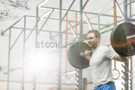 Muscle training : Smiling man lifting barbell at crossfit gym