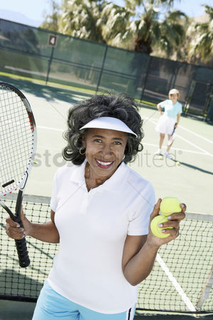 Match : Smiling senior woman holding tennis balls and racket on tennis court