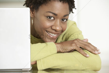 Head shot : Smiling woman using laptop