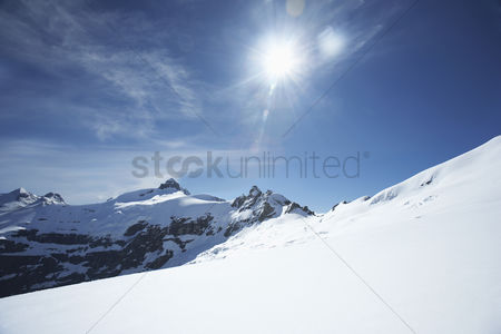 Remote : Snow-topped mountain peaks under the sun