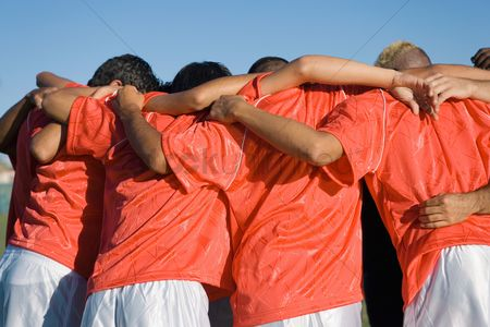 Sports : Soccer team in huddle back view