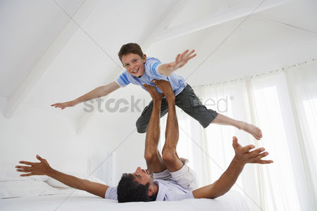 Young boy : Son balancing on father s legs on bed in bedroom