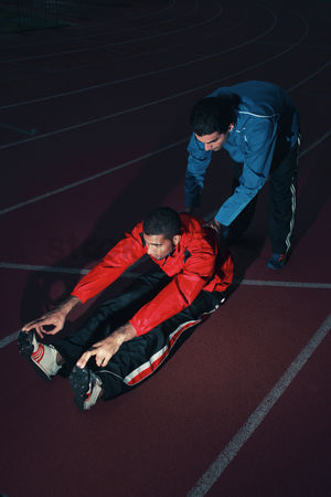 Pushing : Sports coach helping male athlete stretching his body