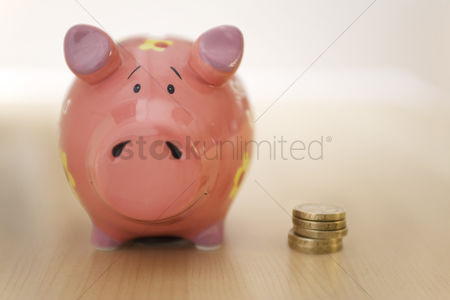 Pocket : Stack of gold coins standing next to piggy bank