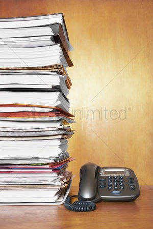 Pile : Stack of paperwork and telephone on desk