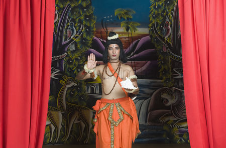 God : Stage artist dressed-up as rama blessing and holding a conch shell