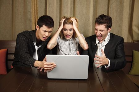Frowning : Stressed business people looking at laptop