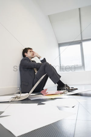 Loss : Stressed businessman sitting on floor of empty office by scattered files