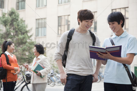 Advice : Students discussing and looking at the book  another student talking with professor on the background