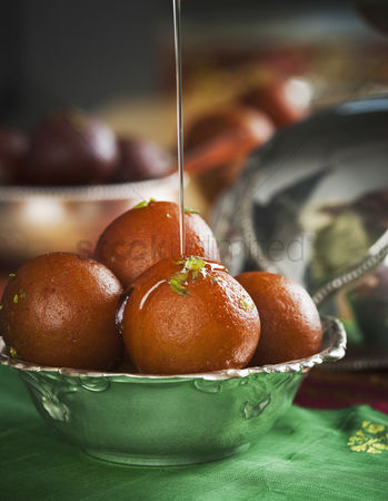 Diwali : Sugar syrup being poured on gulab jamuns in a bowl